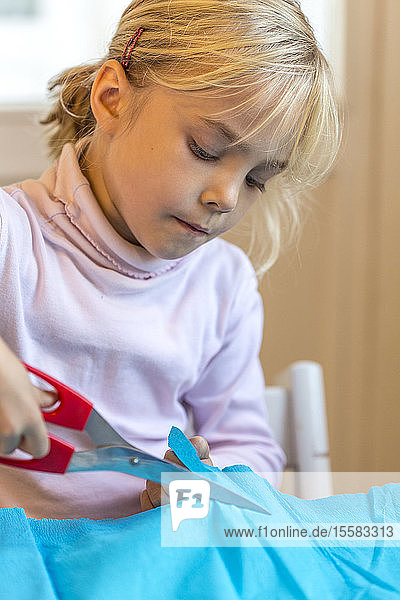 Little girl tinkering with scissors and crepe paper