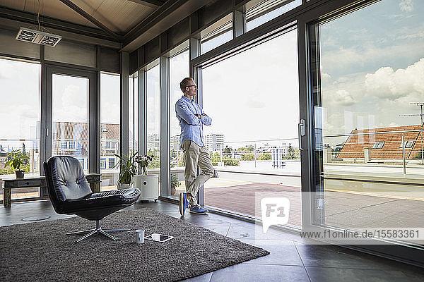Junger Mann steht an Balkontür und schaut hinaus