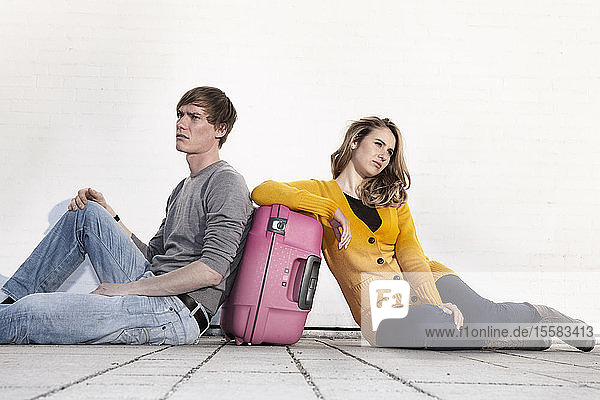 Germany  Bavaria  Munich  Young couple waiting with suitcase