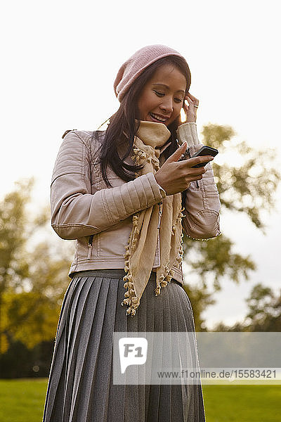 Deutschland  Köln  Junge Frau mit Handy im Park  lächelnd