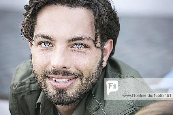 Deutschland  Köln  Junger Mann lächelt  Porträt