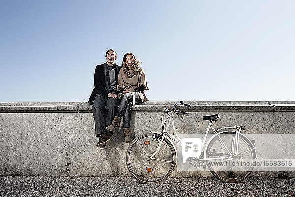 Germany  Bavaria  Munich  Young couple sitting on wall with bike