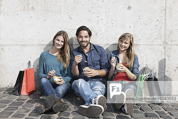 Germany  Cologne  Young man and with ice cream and shopping bags  smiling  portrait