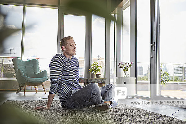 Young man sitting on carpet at home looking out of window