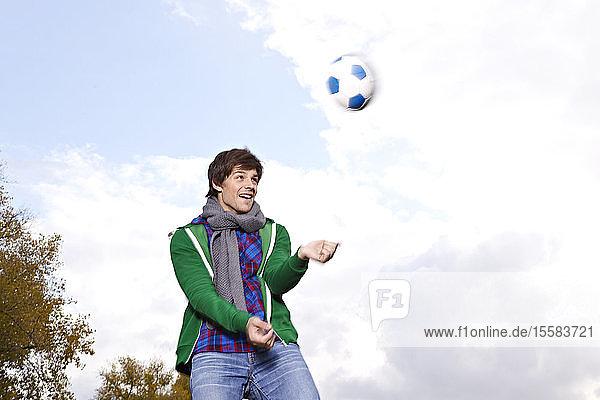 Deutschland  Köln  Junger Mann spielt mit Fussball  lächelnd