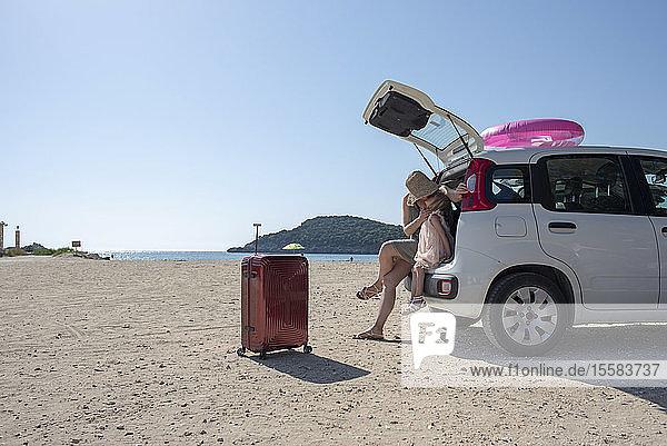 Griechenland  Parga  Mutter küsst Tochter im Kofferraum am Strand