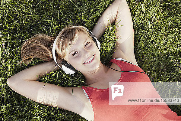 Germany  Cologne  Young woman lying in grass  smiling  portrait