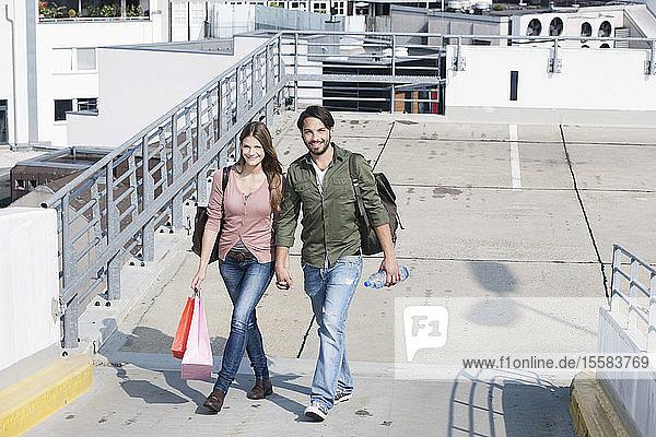 Deutschland  Köln  Junges Paar mit Einkaufstaschen  lächelnd  Porträt