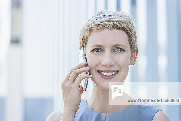 Portrait of smiling blond woman telephoning with smartphone