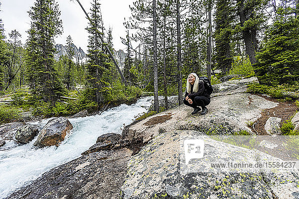 Mature woman crouching on rocks by river in Stanley  Idaho  USA