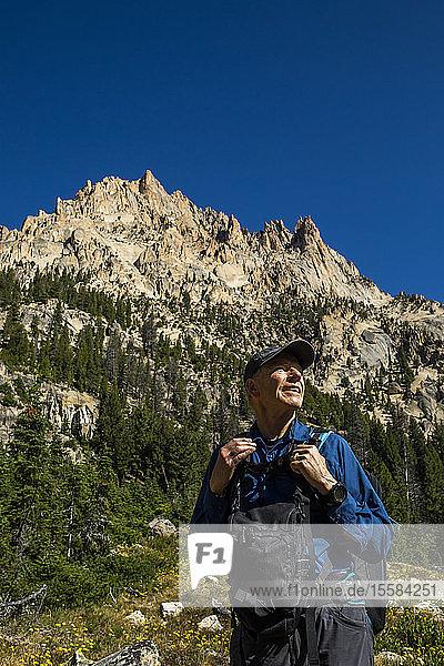 Smiling man hiking on Sawtooth Mountains in Stanley  Idaho  USA