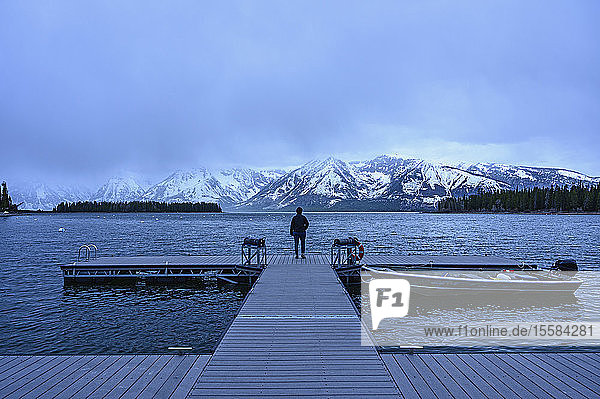 Woman standing on jetty on Jenny Lake in Grand Teton National Park  USA