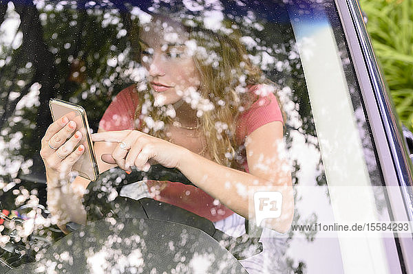 View through car windscreen of young woman using smart phone