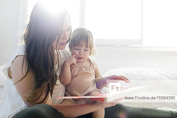 Woman reading book to her daughter on bed