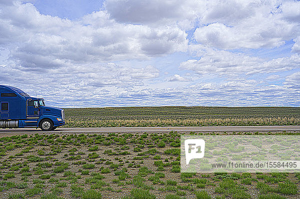 Blue truck on rural highway in Wyoming  USA