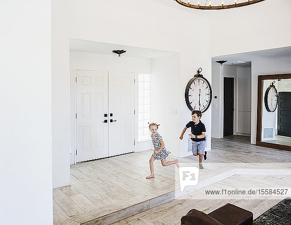 Boy chasing his sister in entrance hall