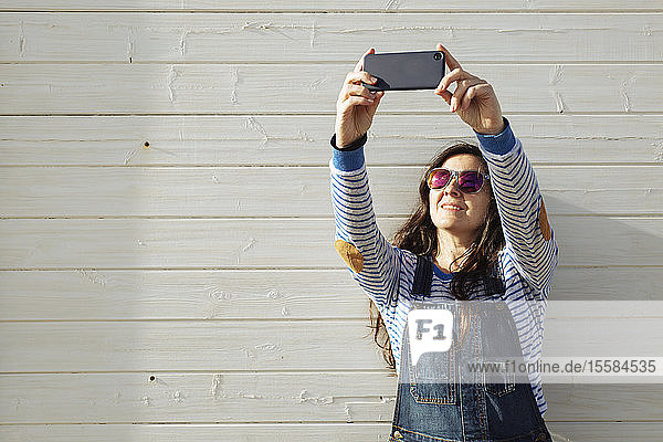Woman wearing sunglasses taking selfie