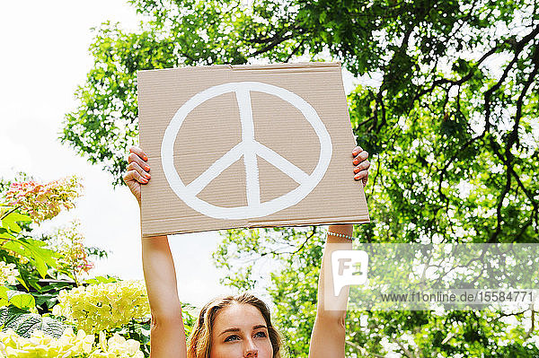 Young woman holding aloft peace symbol