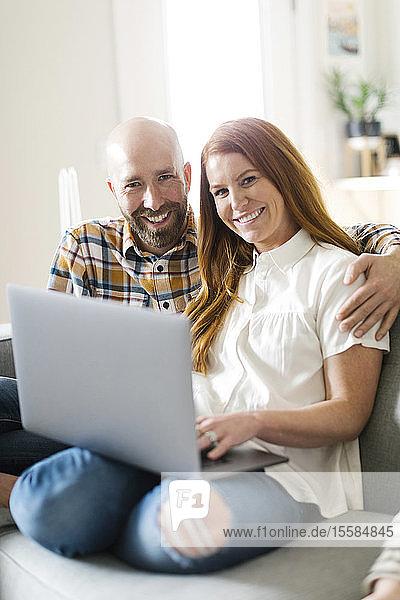 Smiling couple using laptop on sofa