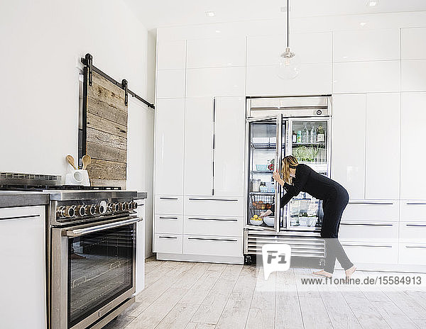 Woman reaching into refrigerator