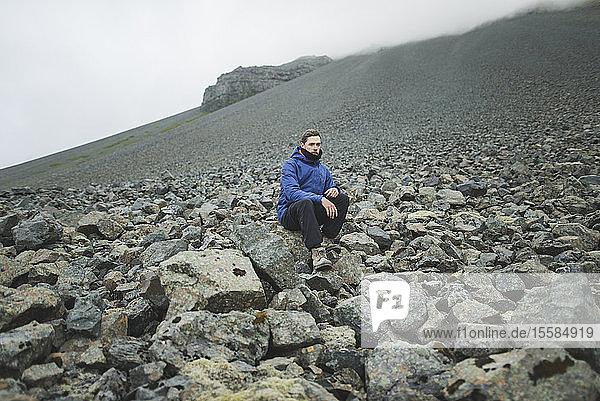 Young man sitting on rock hill in Kirkjubµjarklaustur  Iceland