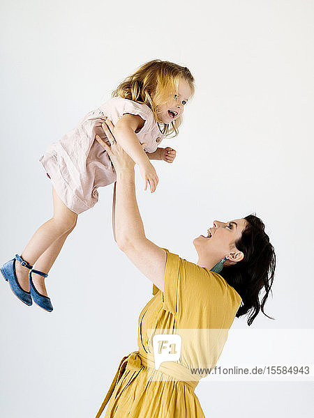 Mother holding her daughter aloft