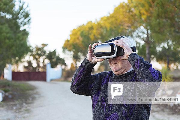 Senior man wearing virtual reality simulator outdoors
