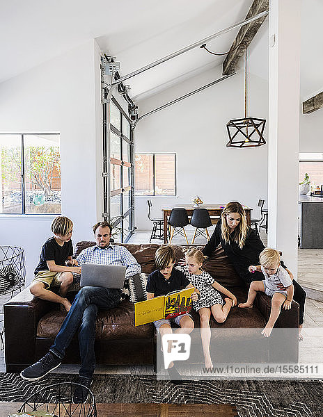 Family with book and laptop on sofa