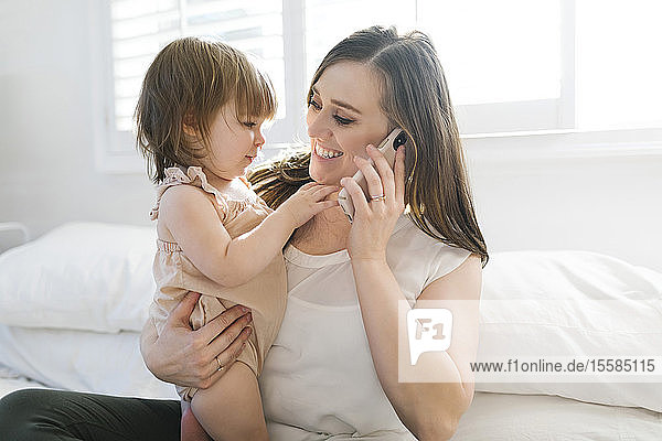 Woman holding daughter while on phone call