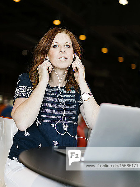 Mid adult woman using laptop and headphones