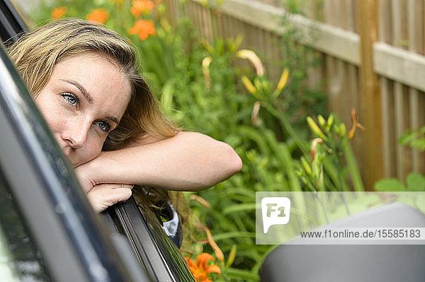 Junge Frau lehnt sich aus dem Autofenster