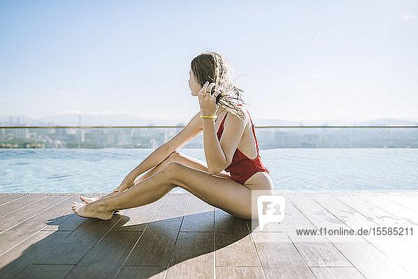 Woman wearing red swimsuit poolside on roof in Kuala Lumpur  Malaysia