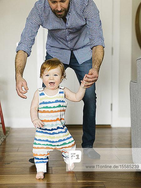 Father helping baby boy to walk