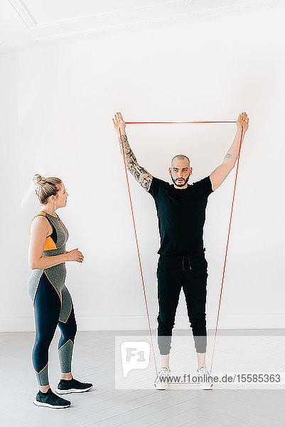 Frau beobachtet Fitnesstrainer bei der Benutzung des Widerstandsbandes im Studio