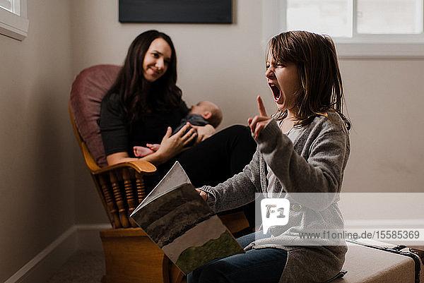 Mädchen mit Buch  das Gesichter zieht  während die Mutter den kleinen Bruder im Wohnzimmersessel wiegt