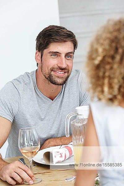 Father listening attentively to daughter at dining table