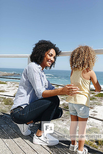 Mother and daughter talking on porch of beach house