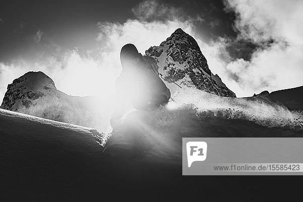 Silhouettenskiläufer beim Skifahren auf einem sonnenbeschienenen Berg  schwarz-weiß  Squamish  Britisch-Kolumbien  Kanada