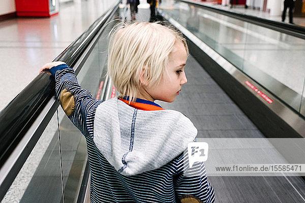 Blondhaariger Junge auf dem Rollsteig am Flughafen  der über die Schulter schaut