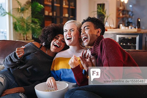 Young man and young female friends laughing while watching tv on living room sofa with bowl of popcorn