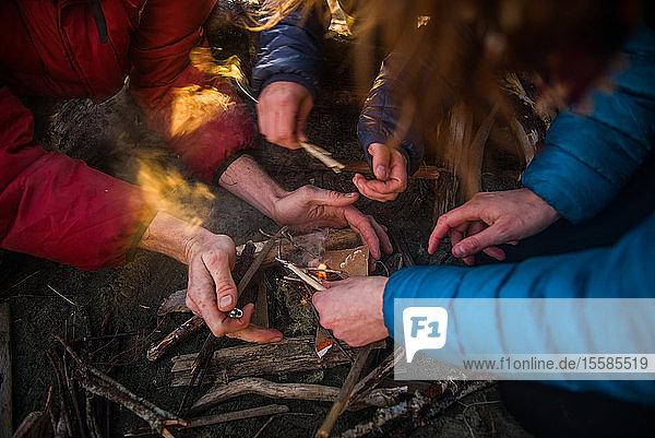 Gruppe von Freunden zündet in der Abenddämmerung ein Lagerfeuer an Cropped  Tofino  Vancouver Island  Kanada