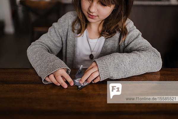 Mädchen am Tisch faltet Papier  macht Origami  Kopf und Schultern
