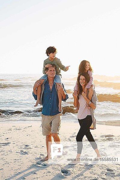 Paar  das Kinder huckepack am Strand mitnimmt
