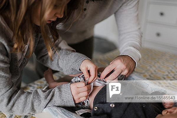 Mädchen mit Vater  der die Windel des kleinen Bruders auf dem Bett wickelt  beschnittene Seitenansicht