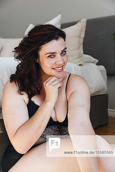 Frau in Dessous posiert im Schlafzimmer
