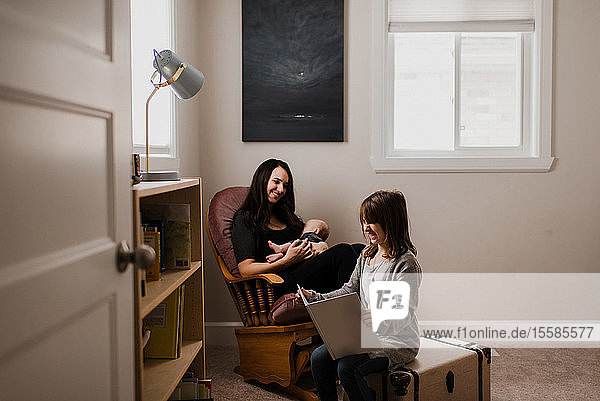 Young woman holding baby son in living room armchair while daughter reads book