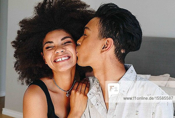 Glückliche junge Frau  die im Schlafzimmer von ihrem Freund auf die Wange geküsst wird  Kopf und Schultern