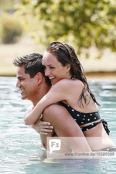 Man giving woman piggyback ride in swimming pool