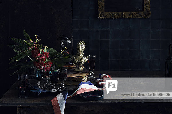 A Bastille Day celebration  tray of glasses with red wine  traditional old master painting and a red white and blue ribbon  colours of the French flag. .