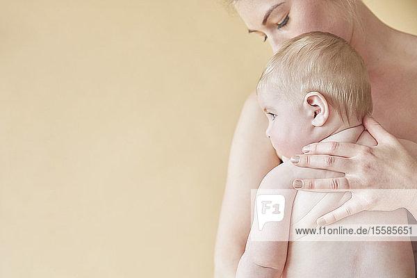 Nackte Mutter tröstet nacktes Baby  das an ihrer Brust liegt
